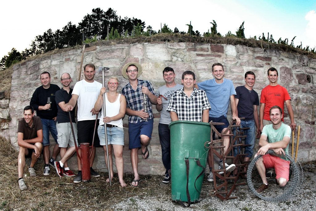 Zu sehen sind 12 Personen, die gemeinsam vor einer Mauer stehen. Sie bilden ein Team und halten jeweils Utensilien für den Wein-Anbau in der Hand. Im Hintergrund ist ein Weingut zu sehen.