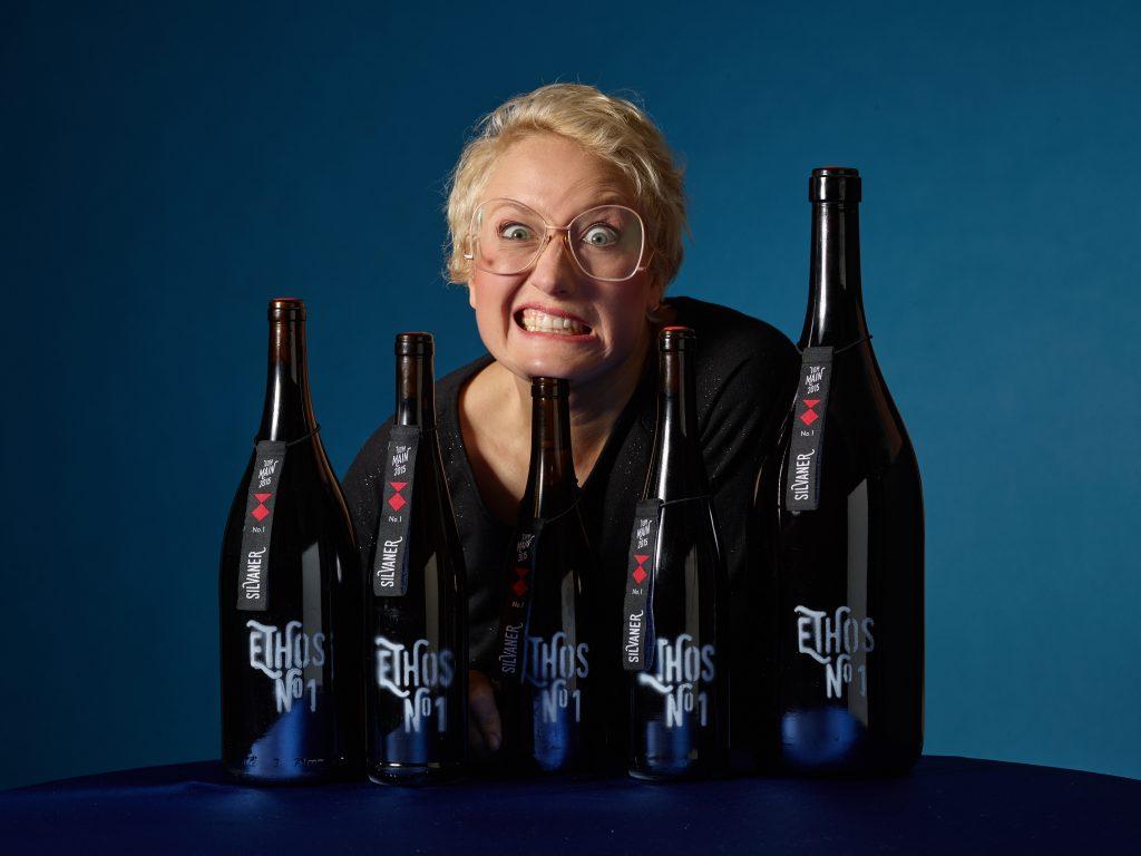 Die blonde Winzerin Ilonka steht hinter 5 Ethos-Weinschlafen und legt Ihren Kopf auf einer Weinflasche ab. Die Flaschen stehen auf einem bauen Tisch, auch der Hintergrund ist blau.