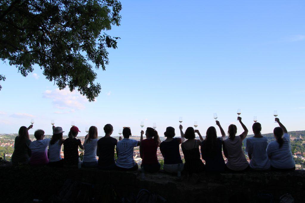 Zu sehen sind viele Menschen auf einer Mauer, die gemeinsam ein Wein-Glas in die Luft heben. Über den Menschen auf der Mauer erstrahlt ein freundlicher Sommerhimmel.
