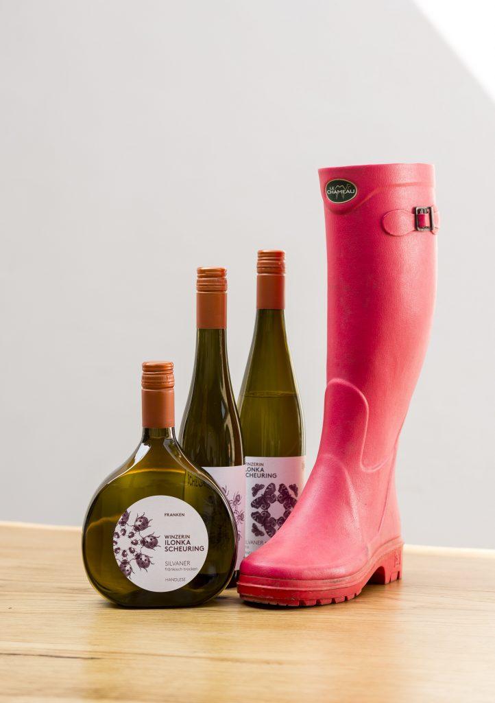 Auf dem Bild sind 3 verschiedene Weinflaschen neben einem pinken Gummistiefel zu sehen. Weinflaschen und Stiefel stehen auf einem hellen Tisch, im Hintergrund befindet sich eine helle Wand.