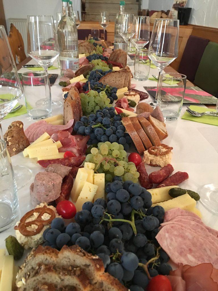 Das Bild zeigt einen reich gedeckten Tisch. Auf der Mitte befinden sich verschiedene Speisen, wie Wurst, Brot und Weintrauben.