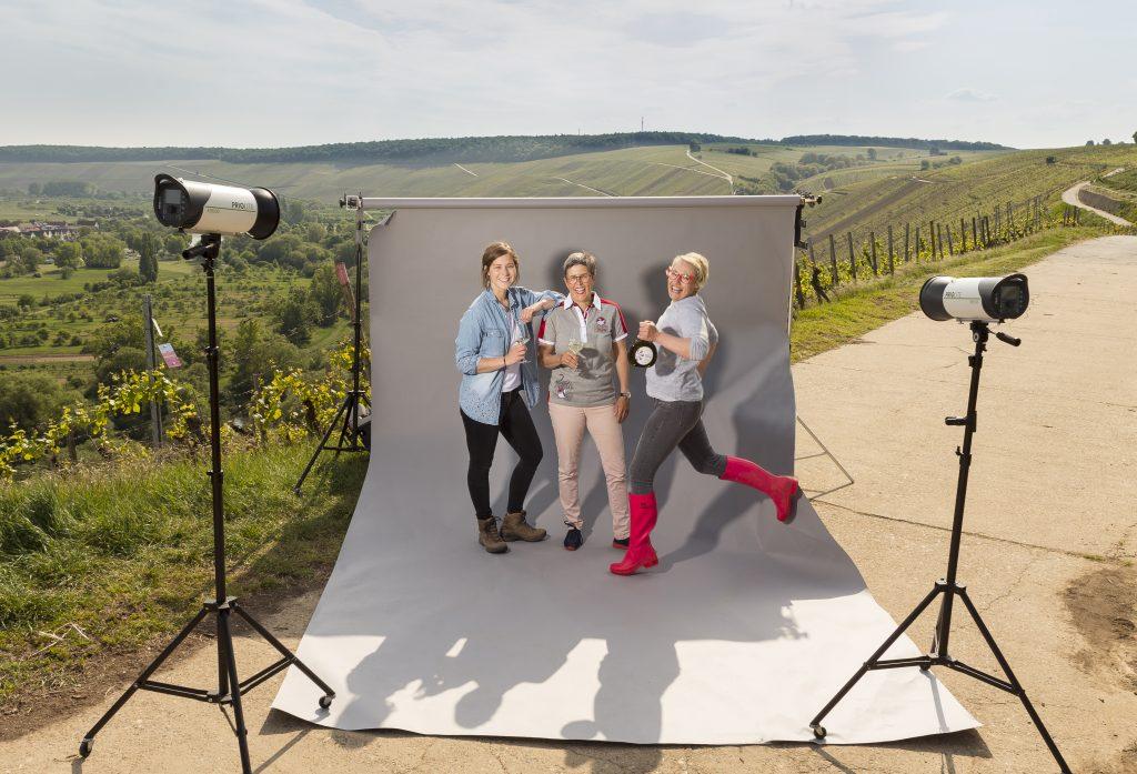 Das Bild zeigt 3 Frauen vor einem Foto-Hintergrund, der in den Weinbergen steht. Dargestellt ist ein Photo-Shooting, im Hintergrund sieht man Weinberge.